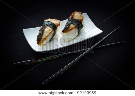Two Nigiri Eel Sushi With Chopstick On Black