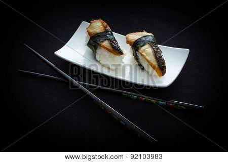 Two Nigiri Eel Sushi And Chopstick On Black