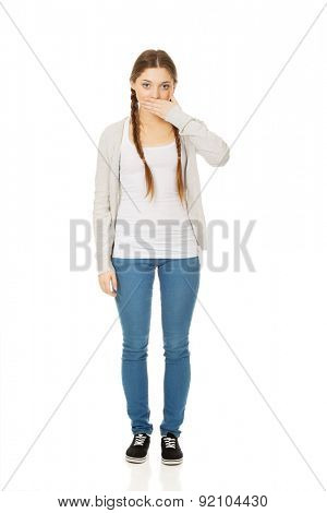 Teen woman covering her mouth with both hands.