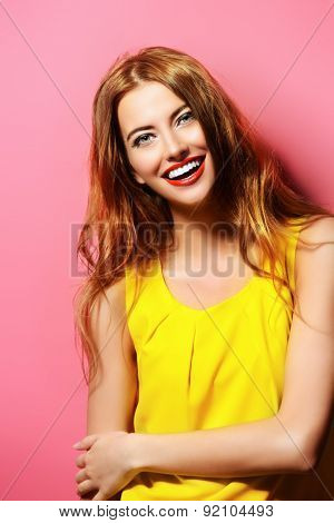Happy emotional young woman in bright yellow dress laughing sincerely. Beauty, fashion concept. Hair, healthy hair.
