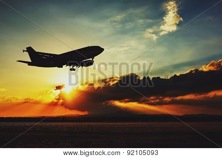 Silhouette of an airplane landing.