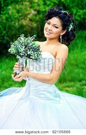 Beautiful elegant asian bride in a summer park. Wedding dress and accessories.