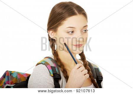Thoughtful teenage girl with schoolbag and pen.