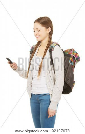 Happy school girl texting to someone.