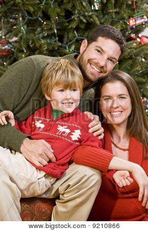 Family With Boy Sitting In Front Of Christmas Tree