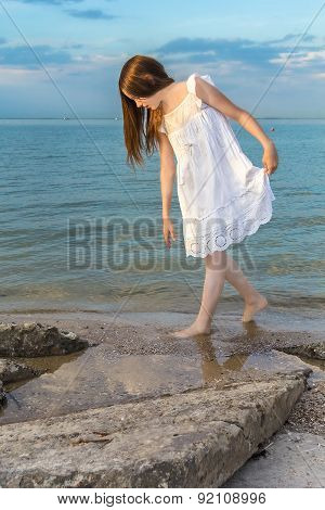 Girl On The Beach Looking For Seashells