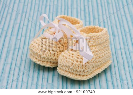 Pale Yellow Baby Booties On Grunge Background