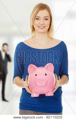 Happy young woman holding piggybank.