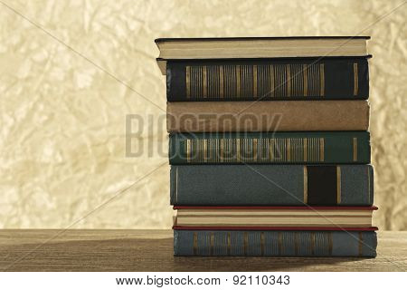 Old books on wooden table on brown background