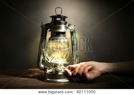 Hand lights a kerosene lamp on dark grey background