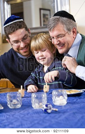 Boy With Father And Grandfather Spinning Dreidel