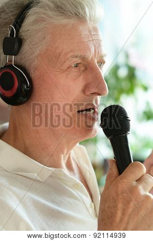 Senior man in headphones singing