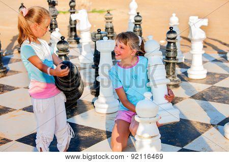 Children playing big chess outdoor.