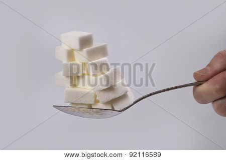 Hand Holding Spoon With Stack Of Sugar Cubes Piled Unhealthy Nutrition, Diet And Sugar Addiction Con