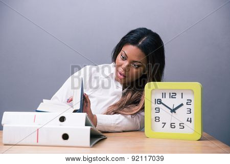 African businesswoman sitting at the table with book and clock over gray background