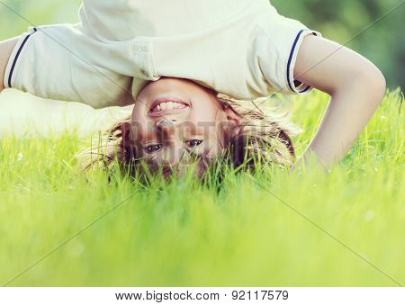 Portraits of happy kids playing upside down outdoors in summer park walking on hands