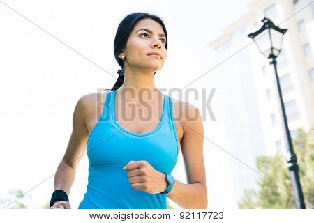 Sports woman running outdoors. Looking away