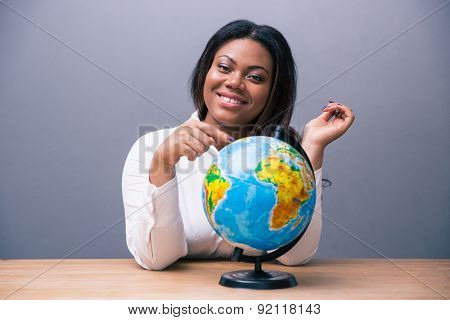 Happy african businesswoman sitting at the table with globe over gray background and looking at camera