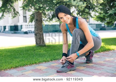 Smiling sporty woman tying her shoelace outdoors and looking at camera