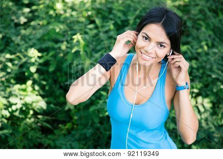 Happy sporty woman in headphones outdoors in park. Looking at camera