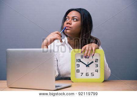 Pensive african american businesswoman sitting at the table with pen and laptop in office over gray background