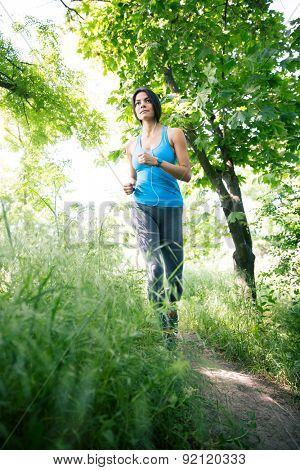 Full length portrait of a cute fitness woman running outdoors in park. Looking away