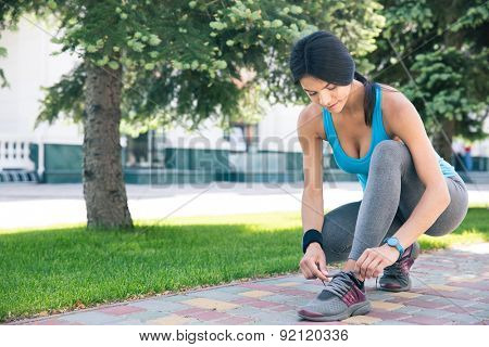 Sports young woman tying her shoelace outdoors
