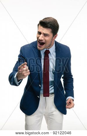 Angry businessman screaming and pointing finger at camera. Isolated on a white background