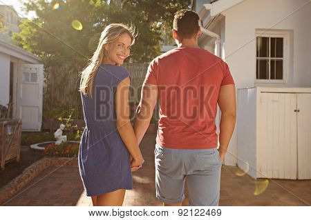 Young Caucasian Couple Walking In The Backyard