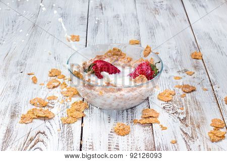 Strawberry Falling In A Bowl With Milk And Cereals.