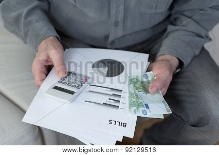 Old Man Holding Bills