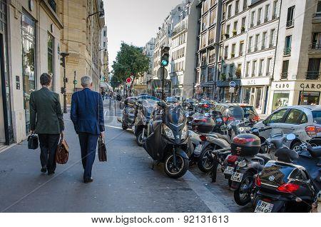 Two male executives walk along Rue de Turbigo in Paris, France