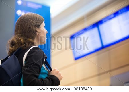 Girl Looking At Airport Flight Information Board