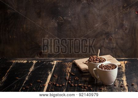 Cup With Coffee Beans At Dark Wooden Background