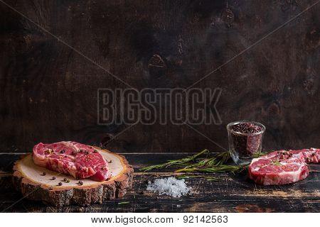 Raw Juicy Meat Steak On Dark Wooden Background Ready To Roasting