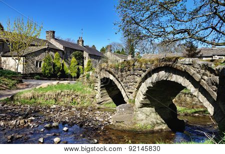 Thirteenth century packhorse bridge and the village of Wycoller.