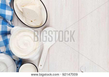 Dairy products on wooden table. Sour cream, milk and cheese. Top view with copy space