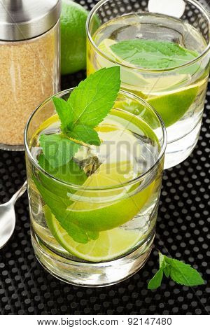 Mojito cocktail and ingredients over black rubber mat