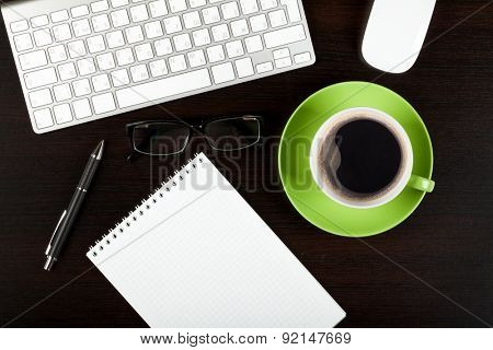 Office desk table with computer, supplies, coffee cup and glasses. Top view with copy space