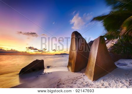 Beautifully shaped granite boulders and a dramatic sunset  at Anse Source d'Argent beach, La Digue island, Seychelles. Vegetation is blurred by a long exposure and a wind