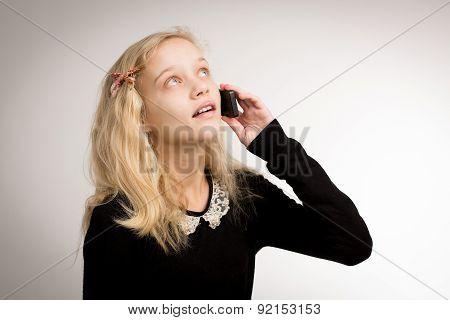 Teenage Girl Talking On Her Phone Looking Up
