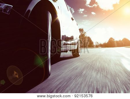 Front Side View Of Black Car Driving Fast