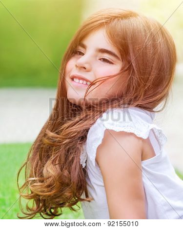 Cute little girl lying down on fresh green grass field; having fun outdoors; relaxing on backyard; happy and carefree childhood