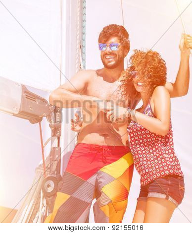 Happy beautiful couple having fun on sailboat, joyful young family enjoying sea traveling, active summer adventure