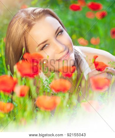 Portrait of cute blond female lying down on fresh poppy field, enjoying beauty of red wild flowers, photo with white copy space, summer holidays in countryside