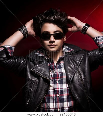 Portrait of cute stylish guy with his hands behind his head over dark red background, wearing fashion clothes and accessories