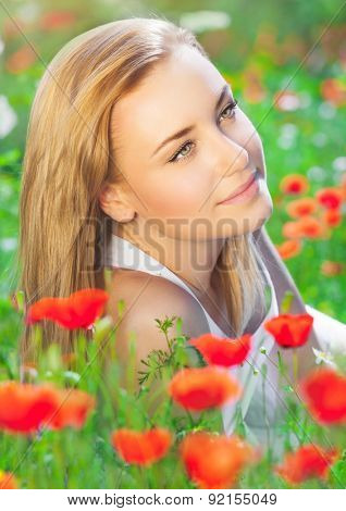 Portrait of beautiful blond woman lying down on fresh poppy field, enjoying beauty of red wild flowers, summer holidays in countryside