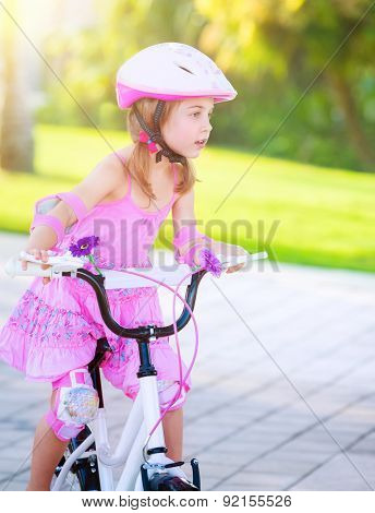 Cute little girl riding a bike in the park in bright sunny day, wearing nice pink dress, enjoying summer sport, happy childhood concept