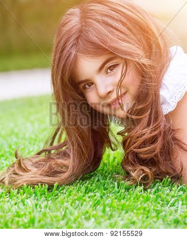 Cute little girl lying down on fresh green grass field, having fun outdoors, relaxing on backyard, happy and carefree childhood