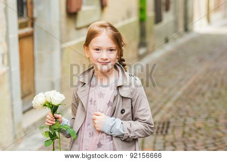 Outdoor portrait of a cute little girl with white roses, wearing beige coat and pink dress